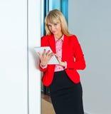 Geschäftsfrau im Bürokorridor mit Tablet-Computer Stockfotos