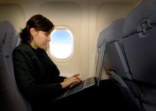 Geschäftsfrau im Flugzeug Stockfotografie