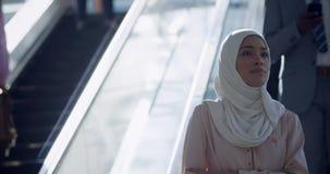 Geschäftsfrau im hijab unter Verwendung der Rolltreppe in einem modernen Büro 4k stock footage
