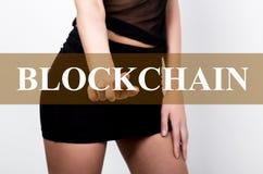 Geschäftsfrau im kurzen Rock, der blockchain Knopf eines virtuellen Schirmes drückt Austausch und Produktion der Schlüsselwährung Lizenzfreie Stockfotos