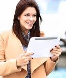 Geschäftsfrau im Mantel, der an digitaler Tablette aus Büro heraus arbeitet stockbild