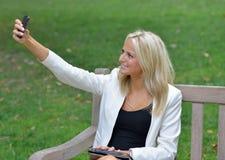 Geschäftsfrau im Park, der ein selfie nimmt Lizenzfreie Stockfotos