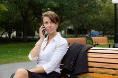 Geschäftsfrau im Park spricht am Handy Stockbilder