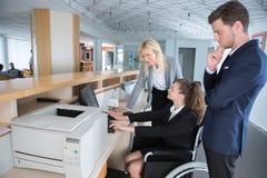 Geschäftsfrau im Rollstuhl, der im Büro arbeitet lizenzfreies stockfoto