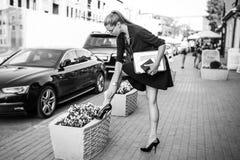 Geschäftsfrau im schwarzen Kleid in der Stadt mit Dokumenten Stockbilder
