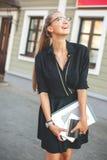 Geschäftsfrau im schwarzen Kleid in der Stadt mit Dokumenten Stockbild