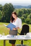 Geschäftsfrau im sonnigen Naturbüro-Blickfaltblatt Stockfotografie