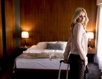 Geschäftsfrau kommt in einem Hotelzimmer mit Koffer an Lizenzfreies Stockfoto