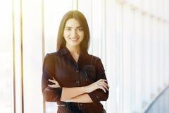 Geschäftsfrau kreuzte Handporträt im Büro mit panormic Fenstern stockfotos