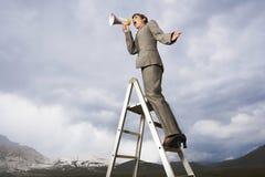 Geschäftsfrau On Ladder Shouting durch Megaphon Lizenzfreie Stockfotos