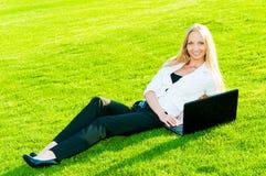 Geschäftsfrau liegt auf dem Gras Lizenzfreie Stockfotos