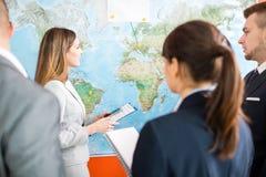 Geschäftsfrau-Looking At World-Karte in Convention Center stockfotos