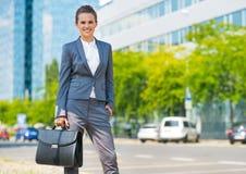 Geschäftsfrau mit Aktenkoffer im Bürobezirk Stockbild