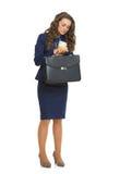 Geschäftsfrau mit dem Aktenkoffer, der auf Uhr schaut stockfoto