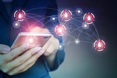 Geschäftsfrau mit dem intelligenten Telefon in der Hand, das an Leute und Technologiehintergrund anschließt Stockbild