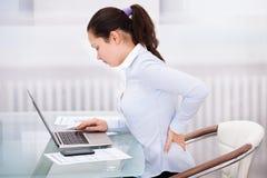 Geschäftsfrau mit dem Laptop, der hinteren Schmerz hat Lizenzfreie Stockbilder