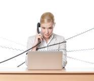 Geschäftsfrau mit dem Laptop gebunden mit Telefonnetzkabel Lizenzfreie Stockfotos