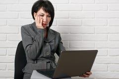 Geschäftsfrau mit dem Laptop und Ordnern, gekleidet in einer grauen Klage wirft vor einer weißen Wand auf Lizenzfreie Stockfotografie