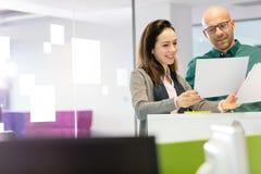 Geschäftsfrau mit dem männlichen Kollegen, der über Dokumenten im Büro sich bespricht Lizenzfreies Stockbild