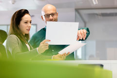Geschäftsfrau mit dem männlichen Kollegen, der über Dokumenten im Büro sich bespricht Stockfotografie
