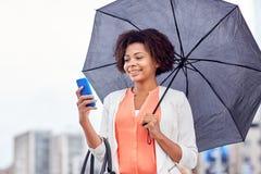 Geschäftsfrau mit dem Regenschirm, der auf Smartphone simst Lizenzfreies Stockbild