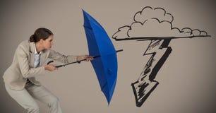 Geschäftsfrau mit dem Regenschirm, der Sturmgraphik gegen braunen Hintergrund blockiert Stockfoto