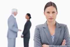 Geschäftsfrau mit den Armen gefaltet und den Kollegen hinter ihr Lizenzfreie Stockfotos