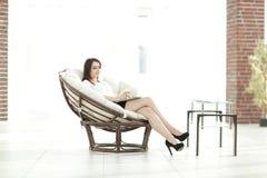 Geschäftsfrau mit den Dokumenten, die ringsum einen bequemen Stuhl sitzen lizenzfreies stockfoto