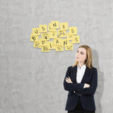 Geschäftsfrau mit den gekreuzten Armen nähern sich Unternehmensplananmerkungen Stockfotos