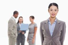 Geschäftsfrau mit den Mitarbeitern, die einen Laptop im backgroun aufpassen Lizenzfreie Stockbilder