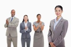 Geschäftsfrau mit den Mitarbeitern, die im Hintergrund applaudieren Stockbilder
