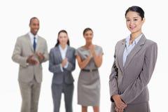 Geschäftsfrau mit den Mitarbeitern, die im Hintergrund applaudieren Stockfoto