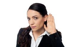 Geschäftsfrau mit der Hand zum Ohr lizenzfreie stockfotos