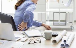 Geschäftsfrau mit der Schmerz Rückseite herein stockfotografie
