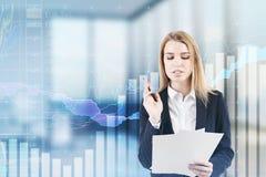 Geschäftsfrau mit Dokumenten und Diagrammen, Büro Stockfotos