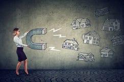 Geschäftsfrau mit einem Magneten, der Hauskäufer und Haushaltsstimmen anzieht stockfoto