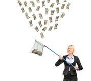Geschäftsfrau mit einem Netz, das versucht, Geld abzufangen Stockbild