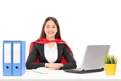 Geschäftsfrau mit einem roten Kap, das an einem Schreibtisch sitzt Stockfoto