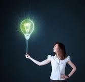 Geschäftsfrau mit einer Ideenbirne Stockbild