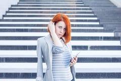 Geschäftsfrau mit einer Tablette in den Händen, die beiseite auf dem Hintergrund der Treppe schauen Stockbild