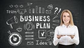 Geschäftsfrau mit einer Tablette nahe Unternehmensplanikonen auf blackboa Lizenzfreie Stockfotografie