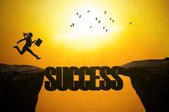 Geschäftsfrau mit Erfolgswort auf der Klippe Stockbild