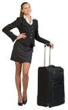 Geschäftsfrau mit fahrbarer Reisetasche, Hand auf Hüfte Lizenzfreie Stockfotografie