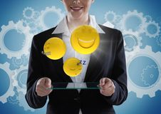 Geschäftsfrau mit Glasgerät und emojis mit Aufflackern gegen blauen Hintergrund mit Gängen Lizenzfreies Stockbild