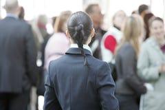 Geschäftsfrau mit großer Gruppe von Personen im Hintergrund stockfotografie