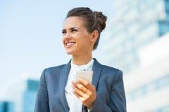 Geschäftsfrau mit Handy im Bürobezirk Lizenzfreie Stockfotografie