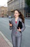 Geschäftsfrau mit Handy und Faltblatt Stockfoto