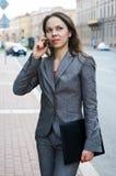 Geschäftsfrau mit Handy und Faltblatt Stockbild