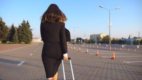 Geschäftsfrau mit ihrem Koffer, der vom Flughafen geht, Parken mit einem Taxi zu fahren Dame, die mit ihrem Gepäck entlang Stadts stock footage