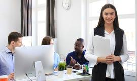 Geschäftsfrau mit ihrem Personal, Leutegruppe im Hintergrund im modernen hellen Büro lizenzfreie stockbilder